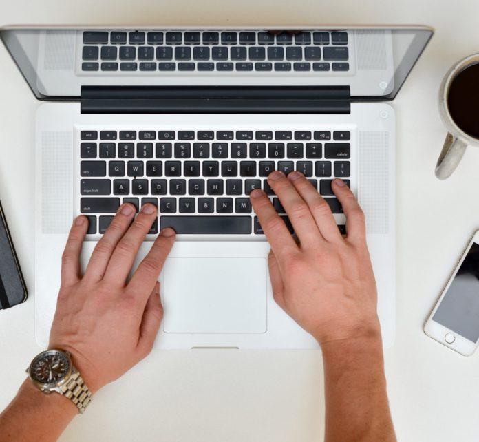 Writing at computer keyboard