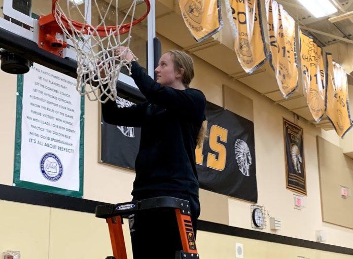 Sage Kramer cutting down basketball net