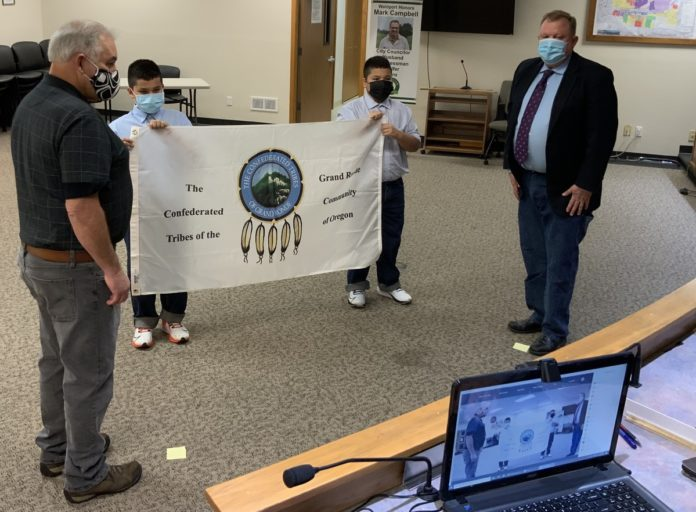 Jacoby and Julian Jones with Grand Ronde flag