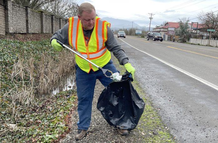 Eric Niemann picking up trash along highway