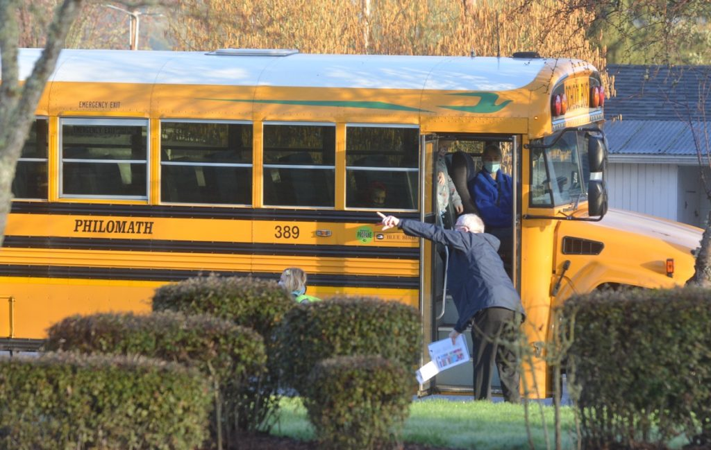Student climbs off school bus