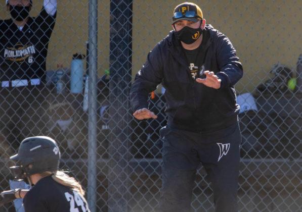 Coach Travis King holds up base runner
