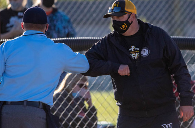 Coach Travis King bumps elbows with umpire