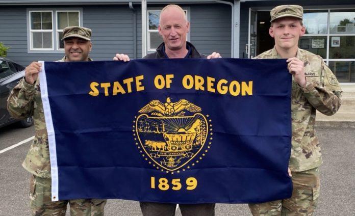 Jamel Mercado, Garry Black and Connar Kohn holding state flag