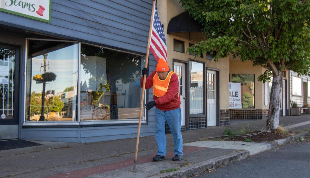 The Philomath Rotary Club's Mal Miner places a flag on Main Street