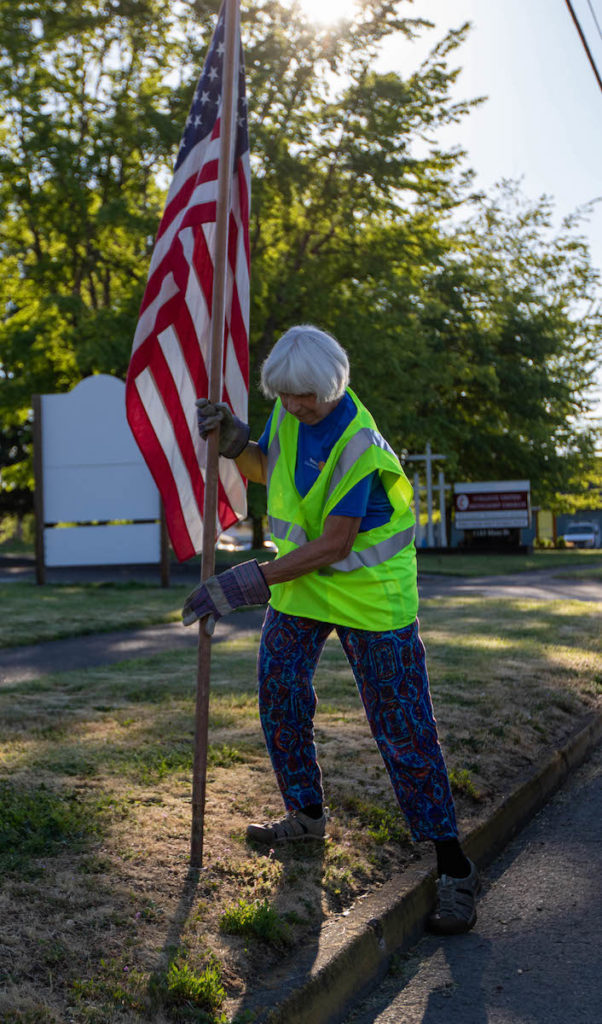 Lindy Young, Philomath Rotary Club president, places a flag by the museum