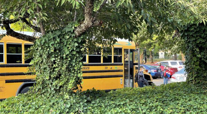 Middle school students disembark school bus